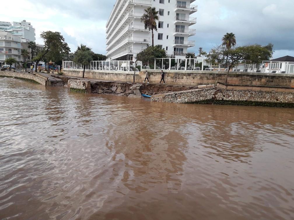 Pessoas caminham nesta quarta-feira (10) pela orla danificada pelas fortes chuvas que atingiram Mallorca, na Espanha  — Foto: Joan Camacho via Reuters
