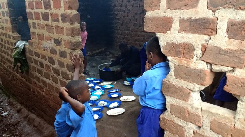 Escola e casas do vilarejo não possuem mesa - os pratos ficam sobre o chão. (Foto: Escola em Uganda)