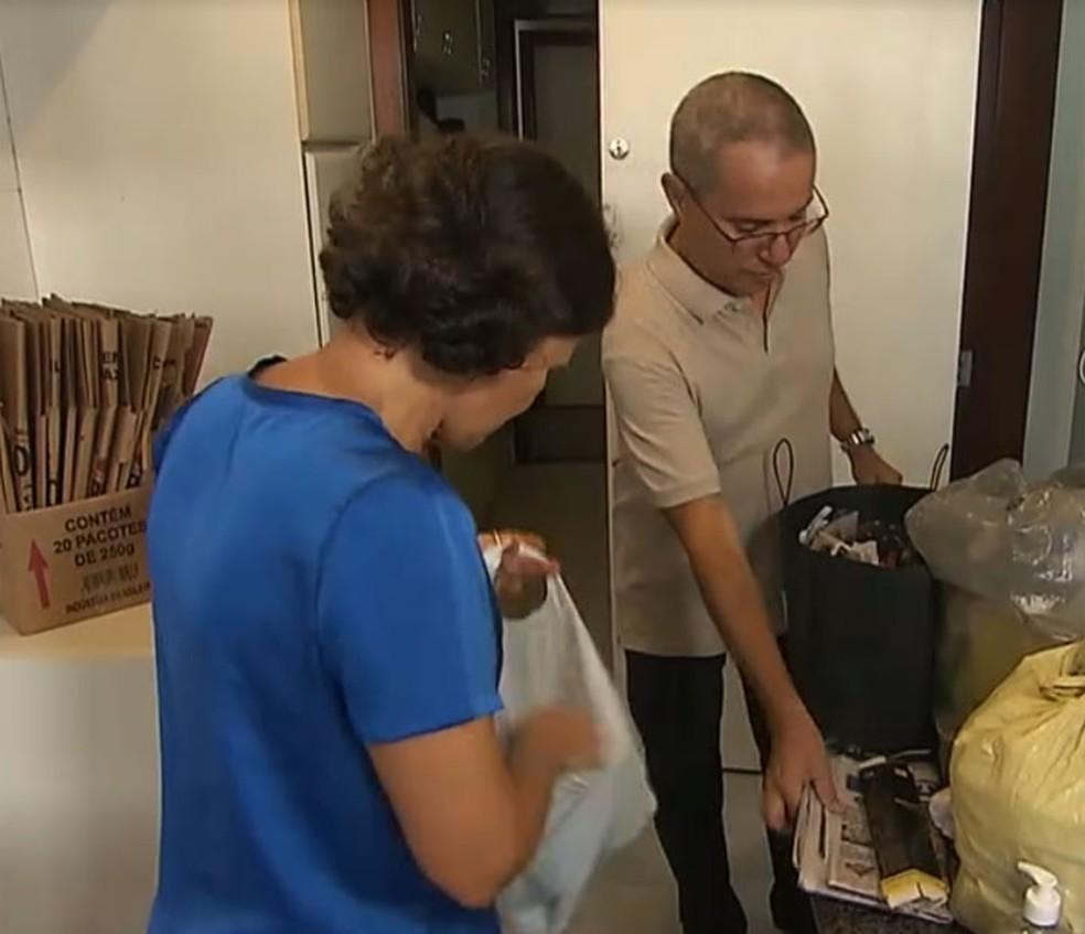 Casal separando material reciclável para entregar em posto da Coelba e ter desconto na conta de luz em Salvador — Foto: Reprodução/TV Bahia