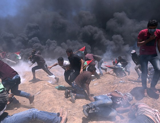 Manifestantes palestinos fogem de ataques de bombas e de gás lacrimogêneo pelas forças de Israel, durante protestos contra decisão dos Estados Unidos de mudar embaixada para Jerusalém (Foto: IBRAHEEM ABU MUSTAFA/REUTERS)