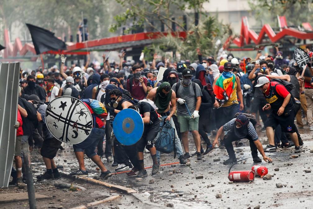 Protesto violento no centro de Santiago, no Chile, nesta sexta-feira (8) tem manifestantes atirando extintores de incêndio e fazendo escudos com objetos — Foto: Jorge Silva/Reuters