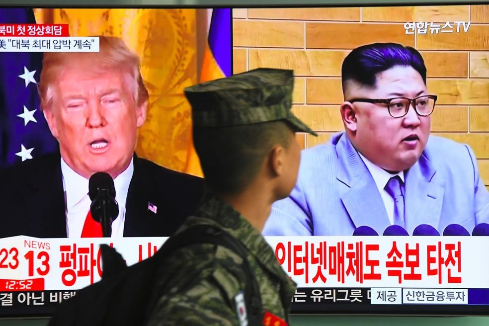 Um soldado sul-coreano passa por uma tela de televisão mostrando imagens do presidente norte-americano Donald Trump e do líder norte-coreano Kim Jong-un em uma estação ferroviária em Seul, na Coreia do Sul. O presidente Donald Trump concordou em ter um encontro histórico com o norte-coreano Kim Jong-un em um surpreendente desenvolvimento no impasse nuclear entre EUA e Coreia do Norte (Foto: Jung Yeon-je/AFP)