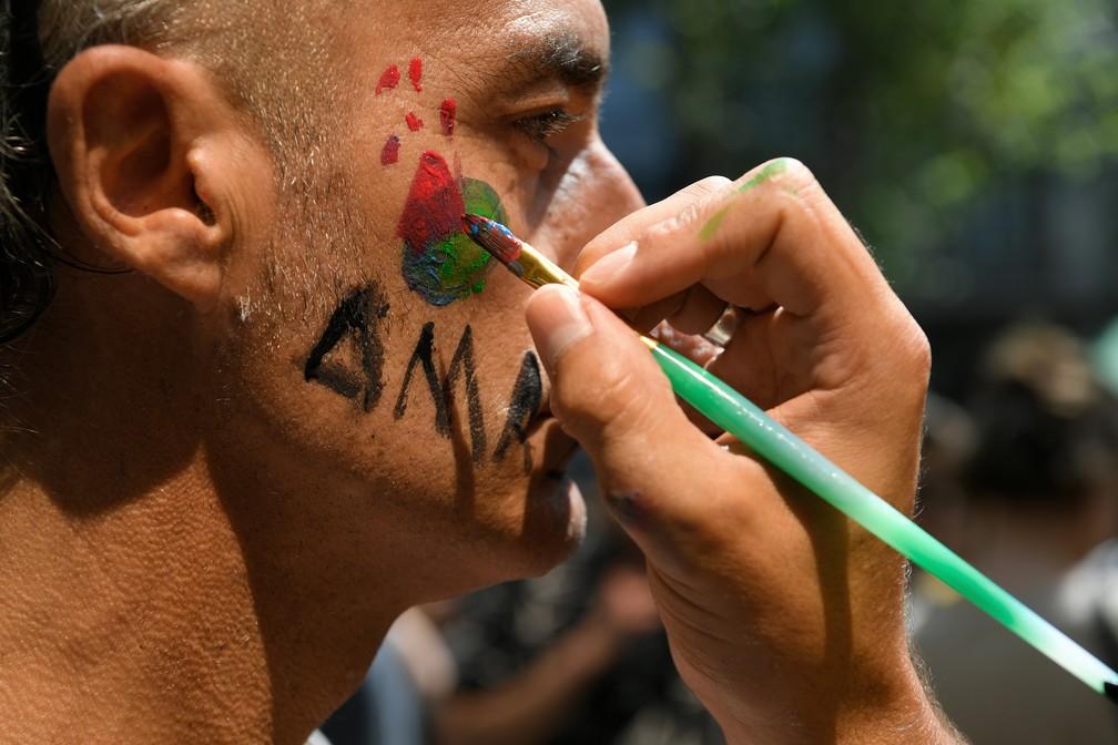 Manifestante pinta o rosto durante protesto nesta sexta (23) em Barcelona, na Espanha. — Foto: Lluis Gene/AFP