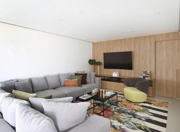 Televisão   O tapete de tear manual é o ponto mais colorido do apartamento, enquanto o sofá em L divide os ambientes (Foto: Mariana Orsi/ Divulgação)