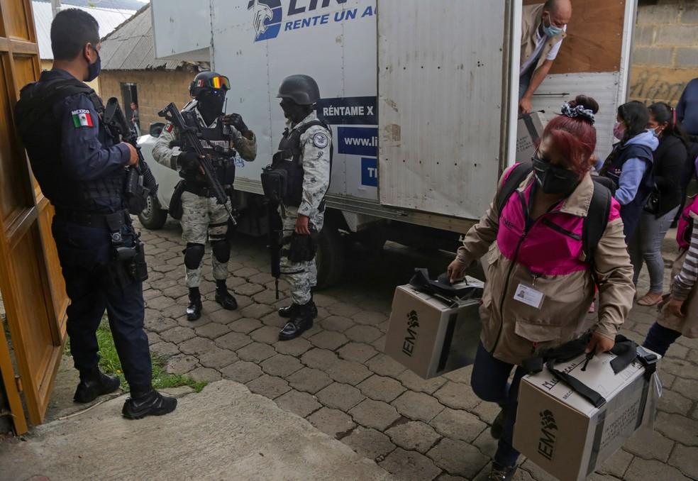 Membros da Guarda Nacional fazem vigilância enquanto trabalhadores do Instituto Nacional Eleitoral (INE) descarregam um caminhão com material eleitoral, a ser distribuído nas seções eleitorais, antes das eleições em Nahuatzen, México, — Foto: Alan Ortega/Reuters