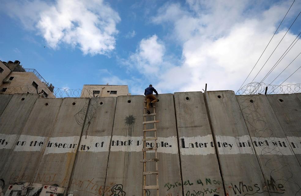 Um palestino usa uma escada para pular um muro israelense perto de Ramallah, Cisjordânia, e tentar chegar às primeiras orações de sexta-feira no mês sagrado islâmico do Ramadã na mesquita Al-Aqsa, em Jerusalém — Foto: Mohamad Torokman/Reuters