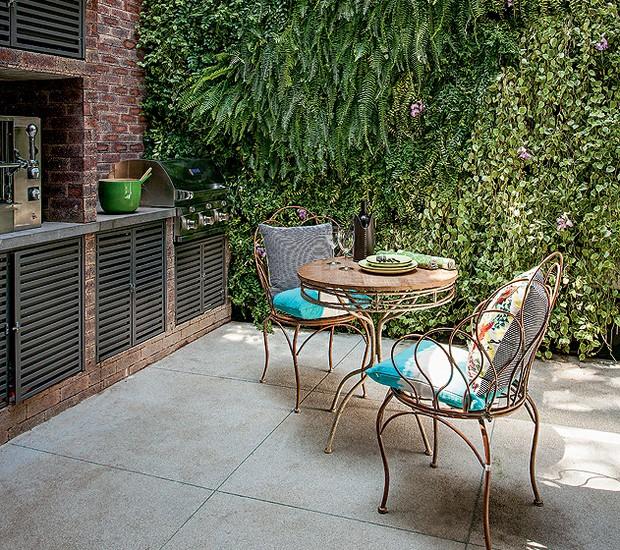 Sala de estar, cozinha e espaço gourmet são integrados, o último do lado de fora. No local, os moradores cozinham, fazem pizza e churrasco. Faltava um jardim. A solução da paisagista Bia Abreu foi revestir a parede com plantas (Foto: Gui Morelli/Casa e Jardim)