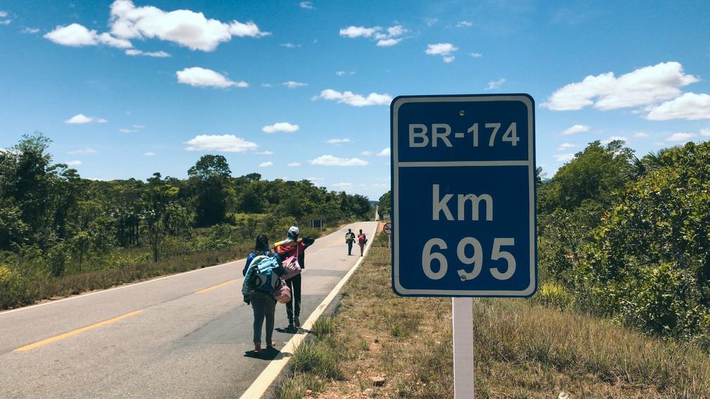 Imigrantes recém-chegados ao Brasil caminham rumo a Boa Vista pela BR-174 (Foto: Inaê Brandão/G1 RR)