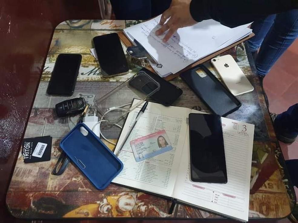 Celulares e documentos apreendidos em cela. — Foto: Polícia Nacional