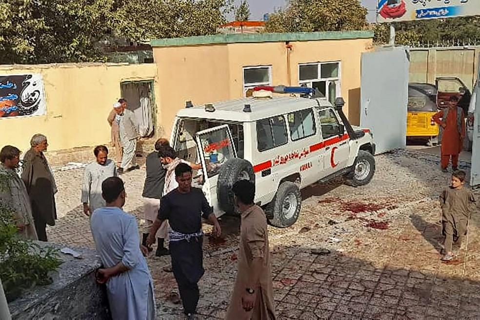 Homens atendem vítimas de uma explosão em uma mesquita xiita no Afeganistão, em 8 de outubro de 2021 — Foto: AFP
