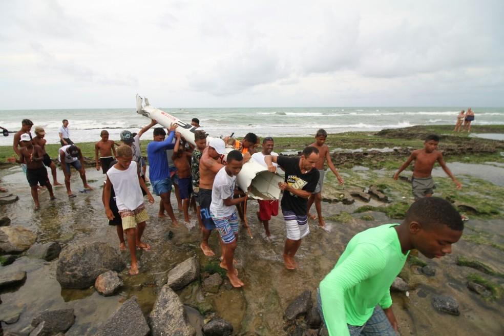Moradores, incluindo crianças, carregam parte da fuselagem do Globocop que caiu nesta terça-feira (23), no Recife (Foto: Aldo Carneiro/Pernambuco Press)