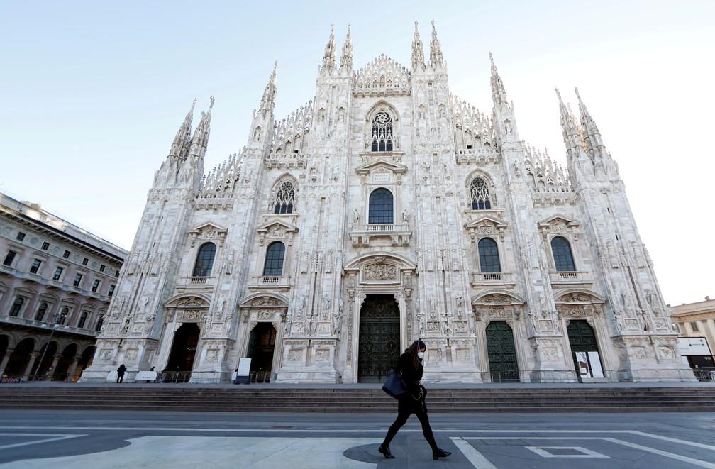 Mulher usando máscara protetora contra o novo coronavírus passa em frente ao Domo, em Milão, no norte da Itália, nesta quinta-feira (27). — Foto: Yara Nardi/Reuters