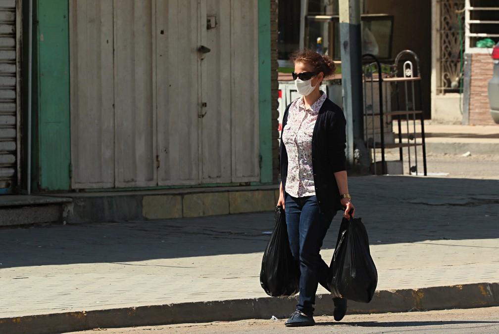 4 de abril - Uma mulher usando máscara passa por lojas fechadas em Bagdá, no Iraque — Foto: Hadi Mizban/AP