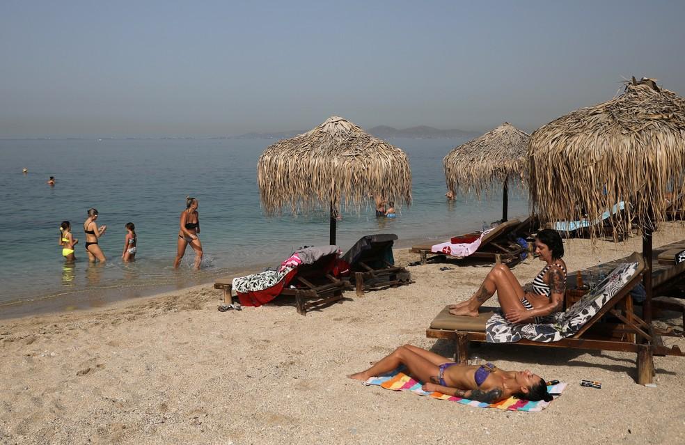 Pessoas aproveitam o sol durante a reabertura oficial das praias ao público, após o alívio das medidas contra a propagação do coronavírus em Atenas, na Grécia. — Foto: Costas Baltas / Reuters