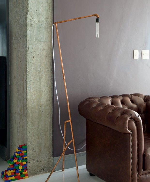 Junto à passagem para a sala de jantar, ficam uma poltrona de couro Chesterfielde uma luminária de chão feita de tubos de cobre pelo próprio morador, em parceria com o Superlimão Studio (Foto: Edu Castello/Editora Globo)