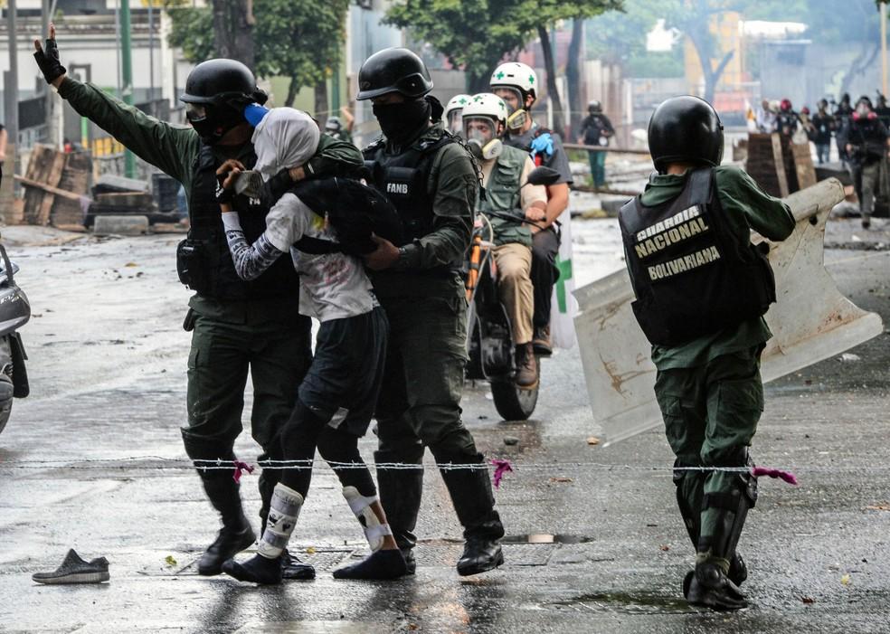 Policiais prendem manifestantes na Venezuela (Foto: Federico Parra/AFP)
