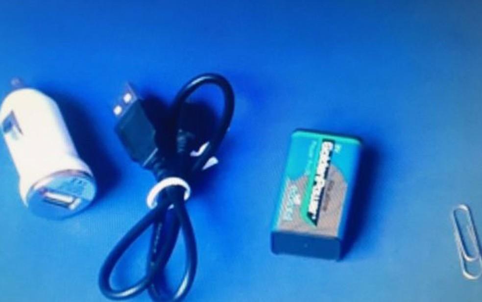Itens essenciais para carregar um celular sem eletricidade: adaptador USB para carros, cabo do próprio telefone, pilha de 9 volts e clipe de metal (Foto: YouTube/Mundo Top)