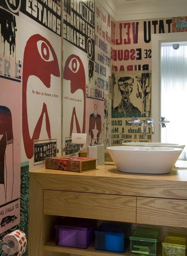 O gabinete de carvalho-americano, desenhado pelo arquiteto Claudio Nomerowska, ocupa toda a extensão da parede principal do lavabo. O grande espelho duplica o efeito do revestimento inusitado, de cartazes tipo lambe-lambe (Foto: Douglas Garcia / Casa e Jardim)