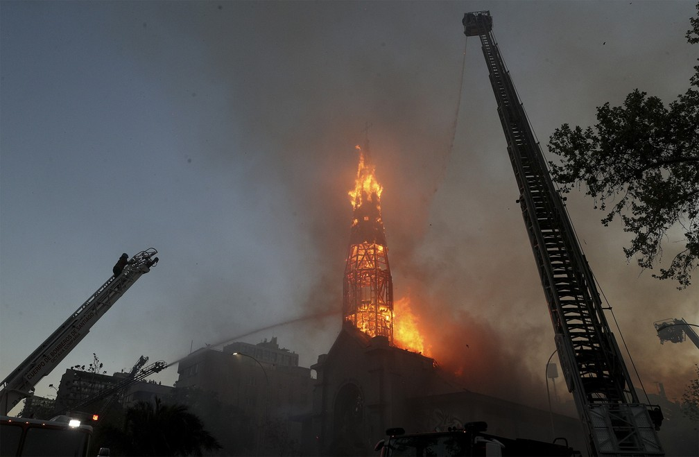 Bombeiros tentam conter o fogo na Igreja La Asunción, incendiada por vândalos encapuzados durante protesto em Santiago, no Chile — Foto: Esteban Felix/AP