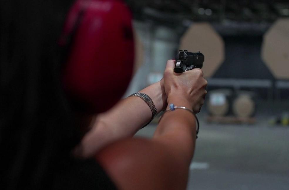 Mulher segura arma de fogo em curso de treinamento de tiro — Foto: TV Globo