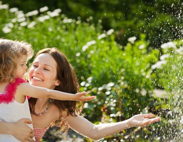 Mãe e filha brincando com água na natureza (Foto: Shutterstock)