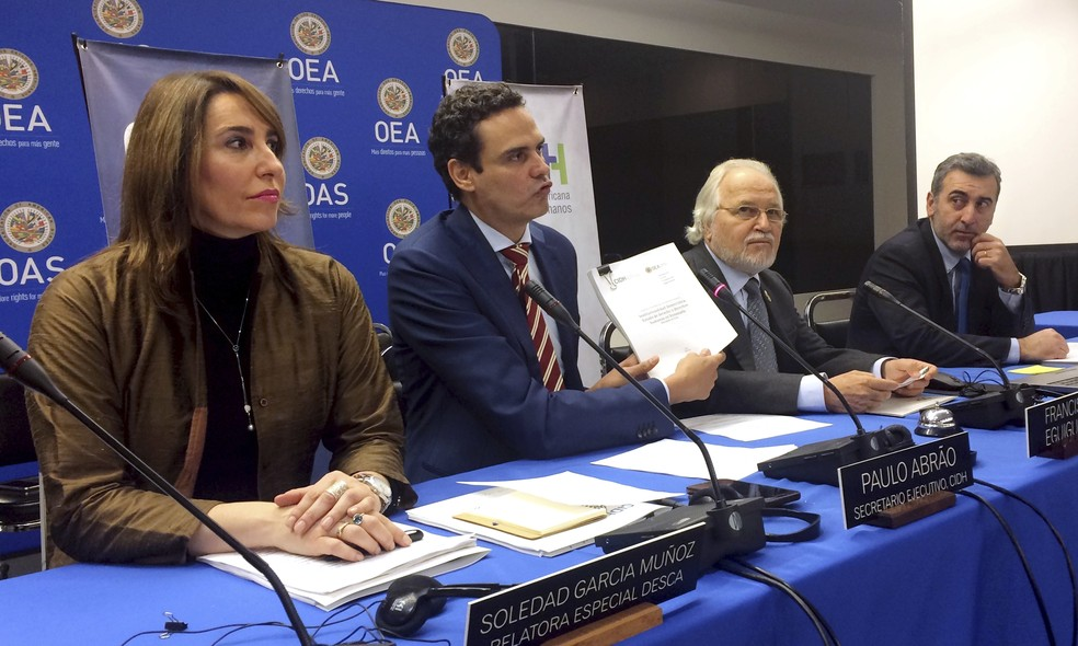 -  Secretário-geral da Comissão Interamericana de Direitos Humanos, Paulo Abrão, segundo da esquerda para a direita, mostra uma cópia de um relatório so