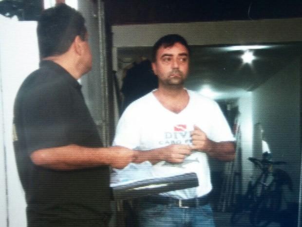 Homem é conduzido por policiais federais durante a operação (Foto: Pedro Figueiredo/TV Globo)