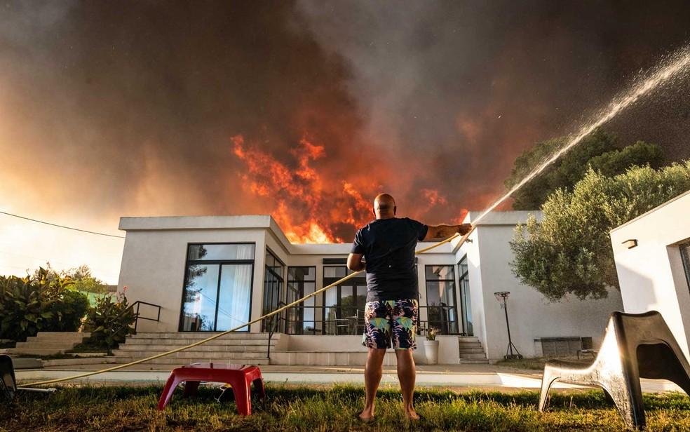 Homem tenta resfriar sua casa no Sul da França — Foto: Xavier Leoty / AFP Photo