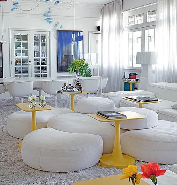 Entre o mar de brancos do apartamento do arquiteto David Bastos, destacam-se as mesas de apoio amarelas, design de Paola Navone. Todo o resto é como a neve: módulos, tapete, paredes, cortina, mesa de jantar e cadeiras (Foto: Tuca Reinés e Denilson Machado/MCA Estúdio)