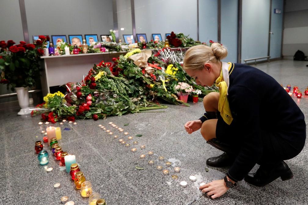 Uma colega dos tripulantes que estavam a bordo do avião que caiu em Teerã coloca uma vela no memorial no aeroporto de Kiev, na Ucrânia, nesta quarta (8). — Foto: Valentyn Ogirenko/Reuters