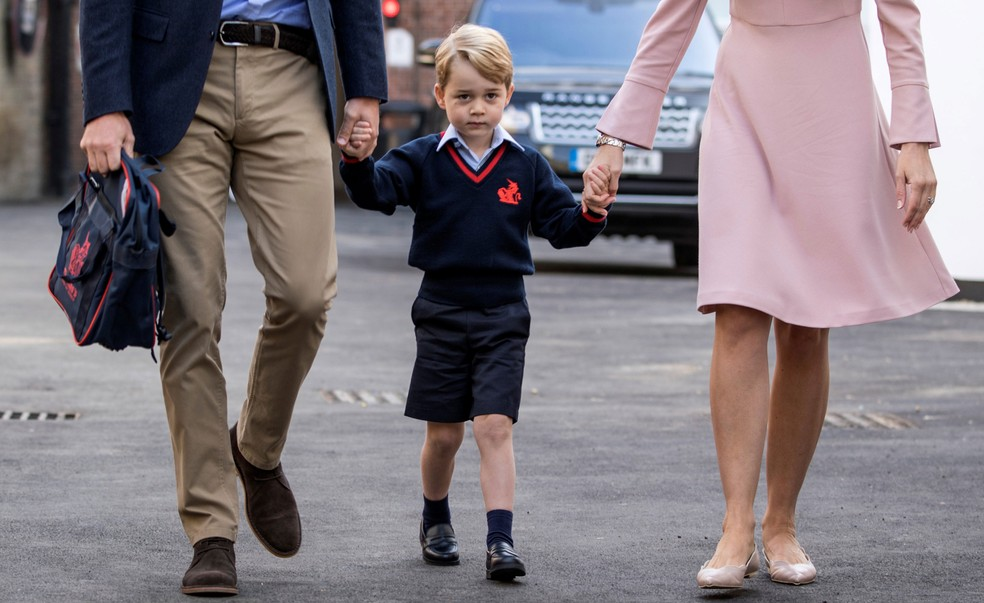 -  Príncipe George segura as mãos do seu pai, príncipe William, e Helen Haslem, diretora da escola em Battersea  Foto: Richard Pohle/Pool/Reuters