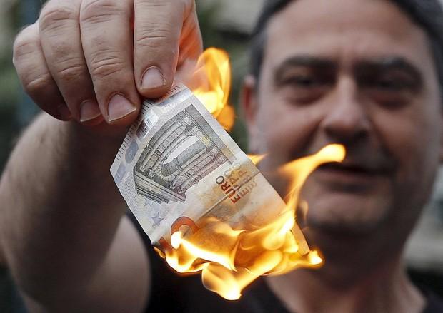 Ένας διαδηλωτής κατά της λιτότητας καίει ένα τραπεζογραμμάτιο ευρώ μπροστά από γραφεία της Ευρωπαϊκής Ένωσης στην Αθήνα την Κυριακή (Φωτογραφία: Reuters / Alex Constantinides)
