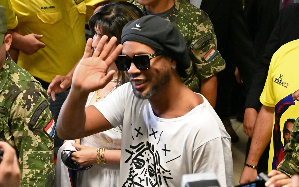 O ex-jogador Ronaldinho Gaúcho acena ao chegar ao Aeroporto Internacional Silvio Pettirossi, em Luque, perto de Assunção — Foto: Norberto Duarte / AFP Photo
