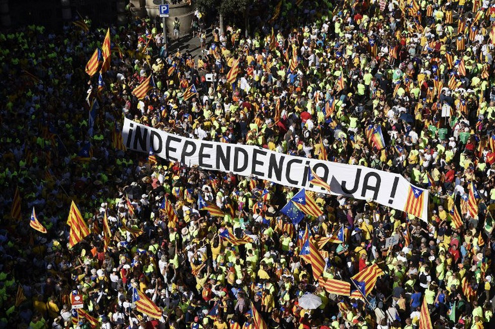 """Manifestantes levam nesta segunda-feira (11) uma faixa com a frase """"Independência Já"""" em Barcelona, na Espanha  (Foto: Josep Lago / AFP)"""