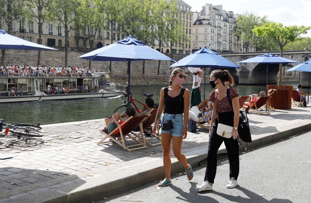 Mulheres usando máscaras caminham ao longo das margens do rio Sena, em Paris, neste sábado, 15 de agosto, enquanto a França reforça o uso de máscaras como parte dos esforços para conter o ressurgimento do coronavírus em todo o país. — Foto: Charles Platiau / Reuters