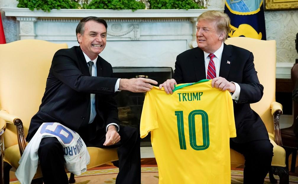 O presidente Jair Bolsonaro entrega camisa da Seleção Brasileira de futebol para Donald Trump; presidente norte-americano também presenteou Bolsonaro — Foto: REUTERS/Kevin Lamarque