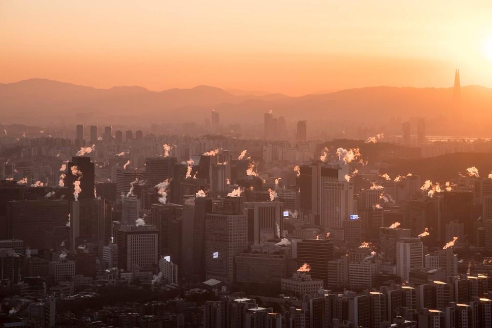 12 de janeiro - Fumaça de aquecedores é emitida do topo de prédios no leste de Seul, na Coreia do Sul, durante o amanhecer (Foto: Ed Jones/AFP)