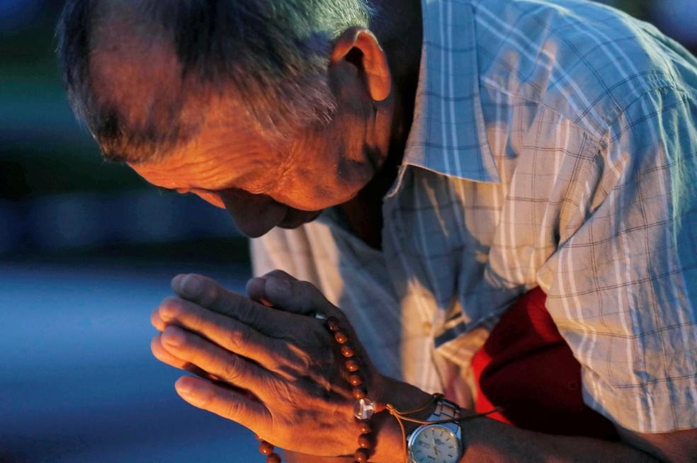 Homem reza por vítimas da bomba de Hiroshima durante cerimônia de homenagem no Japão  (Foto: Kyodo/via REUTERS )