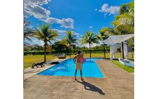 """Antes de entrar no """"BBB"""", o cantor mostrou a área de lazer com piscina de sua mansão. Por ali também fica um barco (Foto: Reprodução)"""