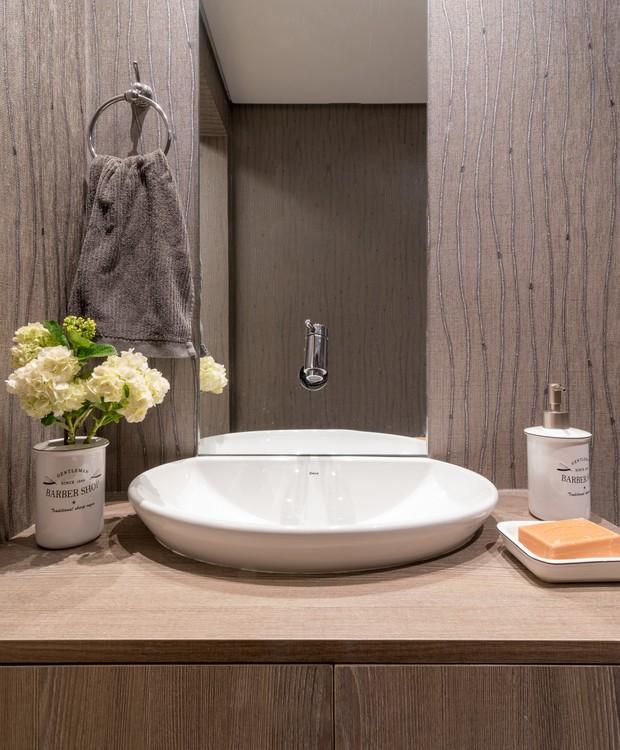 LAVABO   Disfarçado sob o painel de madeira com folha de freijó, o lavabo fica logo ao lado da sala (Foto: Julia Herman/ Divulgação)