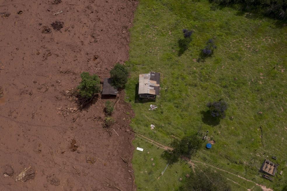 Imagem aérea mostra terreno parcialmente coberto pela lama da barragem da Vale no domingo (27), dois dias após o rompimento — Foto: Mauro Pimentel/AFP