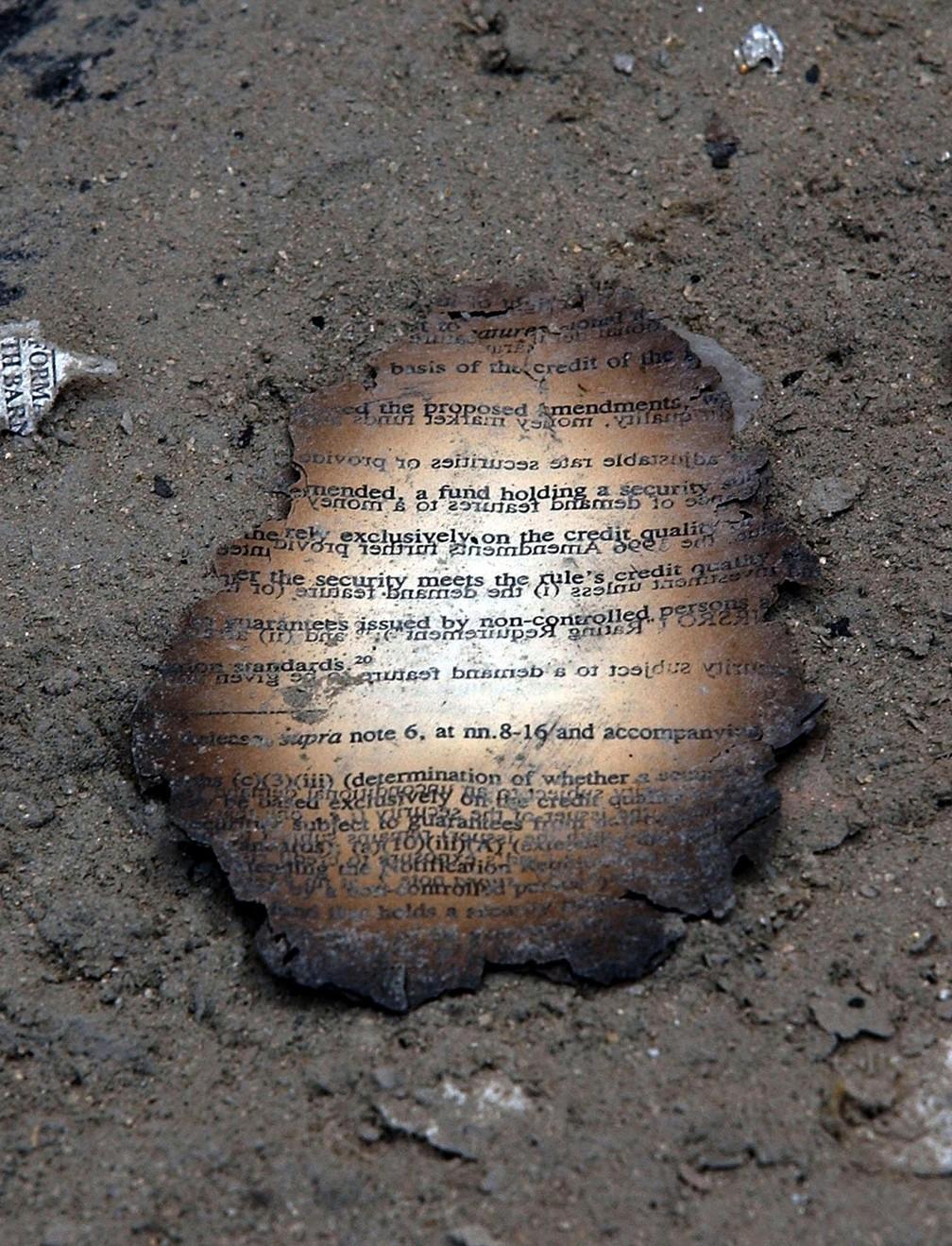 Resto da folha de um documento queimado é visto em meio ao pó que se acumulou nas ruas em área próxima ao World Trade Center, em Nova York, após o atentado terrorista do 11 de Setembro — Foto: Stan Honda/AFP/Arquivo