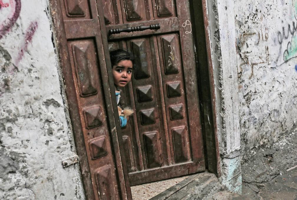 -  Criança palestina olha para fora da porta de uma casa no campo de refugiados de Rafah, no sul da Faixa de Gaza  Foto: Disse Khatib/AFP