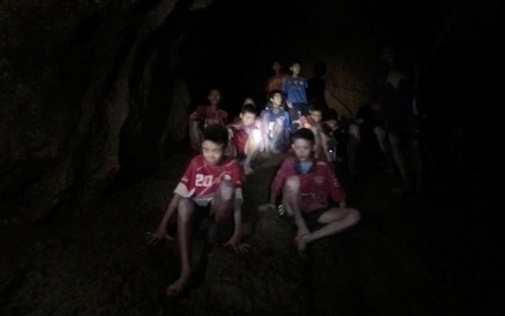 Imagem retirada de vídeo mostra os integrantes do time Moo Pa (ou Wild Boars) e seu técnico, presos na caverna Tham Luang, na província de Chiang Rai, na Tailândia (Foto:  Tham Luang Rescue Operation Center via AP)