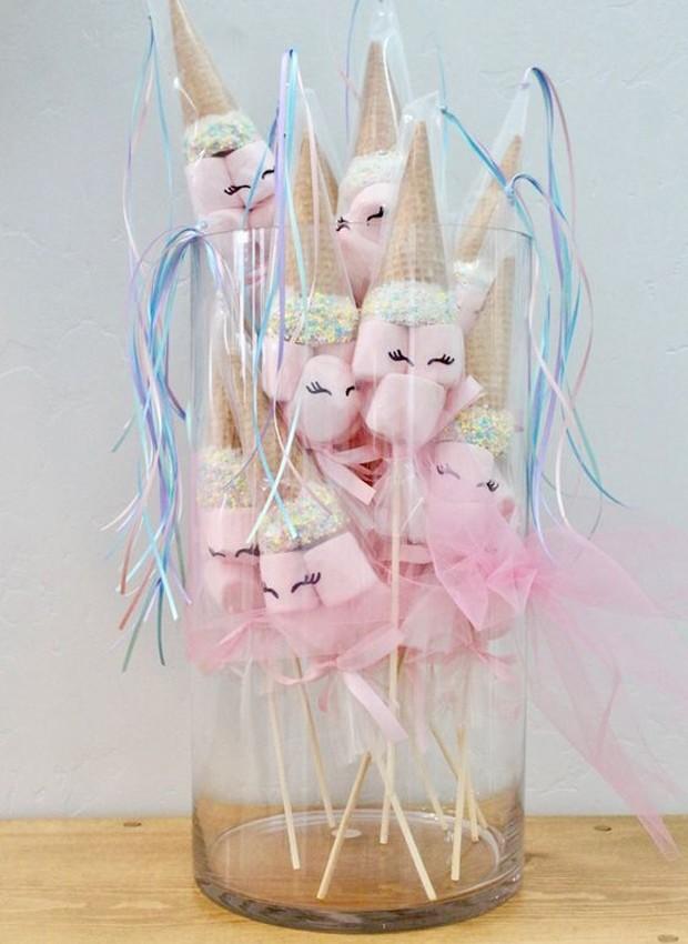 Para unir os marshmellows, um palito fica no centro, enquanto o chifre da criatura é feito de casquinha de sorvete. Para completar, o doce é envolto em uma sacola de tecido rosa, com os olhos do animal (Foto: Pinterest/ Reprodução)