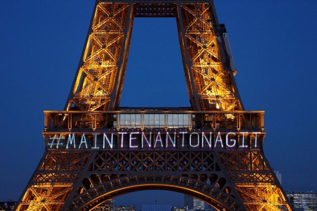"""torre Eiffel, em Paris, recebeu uma iluminação especial com a mensagem """"MaintenantOnAgit"""" (Agora agimos)  (Foto: Geoffroy Van Der Hasselt / AFP)"""