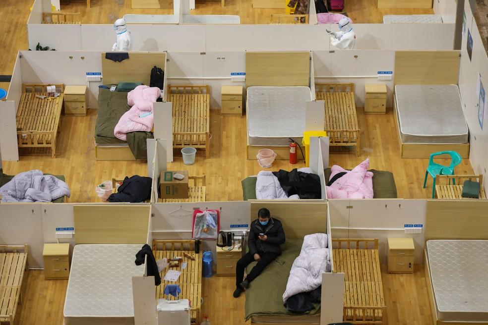 Médicos (na parte de cima da imagem) passam por camas vazias enquanto um paciente descansa em um hospital temporário criado para pacientes com o novo coronavírus COVID-19 em um estádio de esportes em Wuhan, na província central de Hubei, na China — Foto: AFP