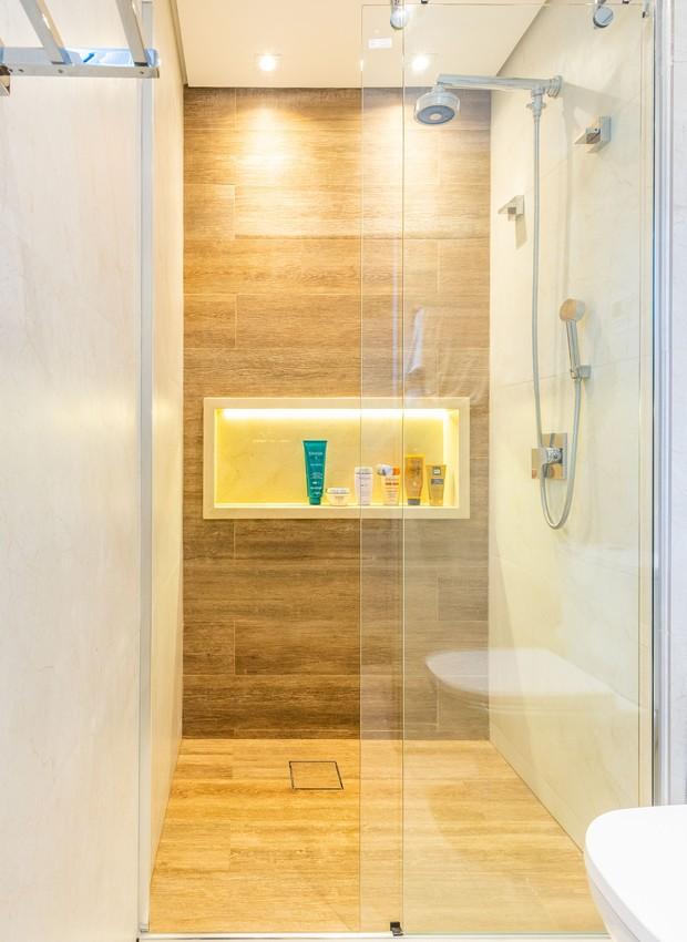 No banheiro da suíte foi utilizado um porcelanato que imita mármore bege e outro que imita madeira, gerando um mix de texturas. (Foto: Fernando Crescenti/Divulgação)