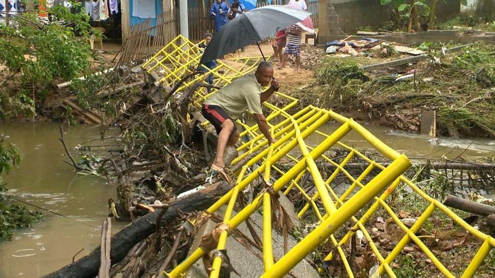 Moradores de Marcílio de Noronha, em Viana, se arriscam passando por passarela que foi derrubada pela chuva — Foto: Reprodução/TV Gazeta