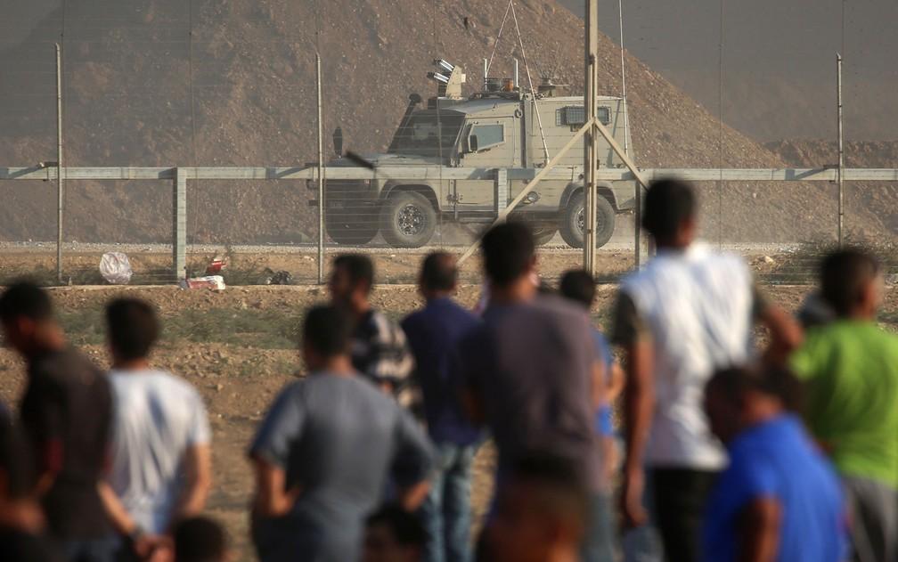Palestinos observam veículo das forças israelenses do outro lado da cerca na fronteira entre Gaza e Israel, na sexta-feira (28) — Foto: Said Khatib/AFP